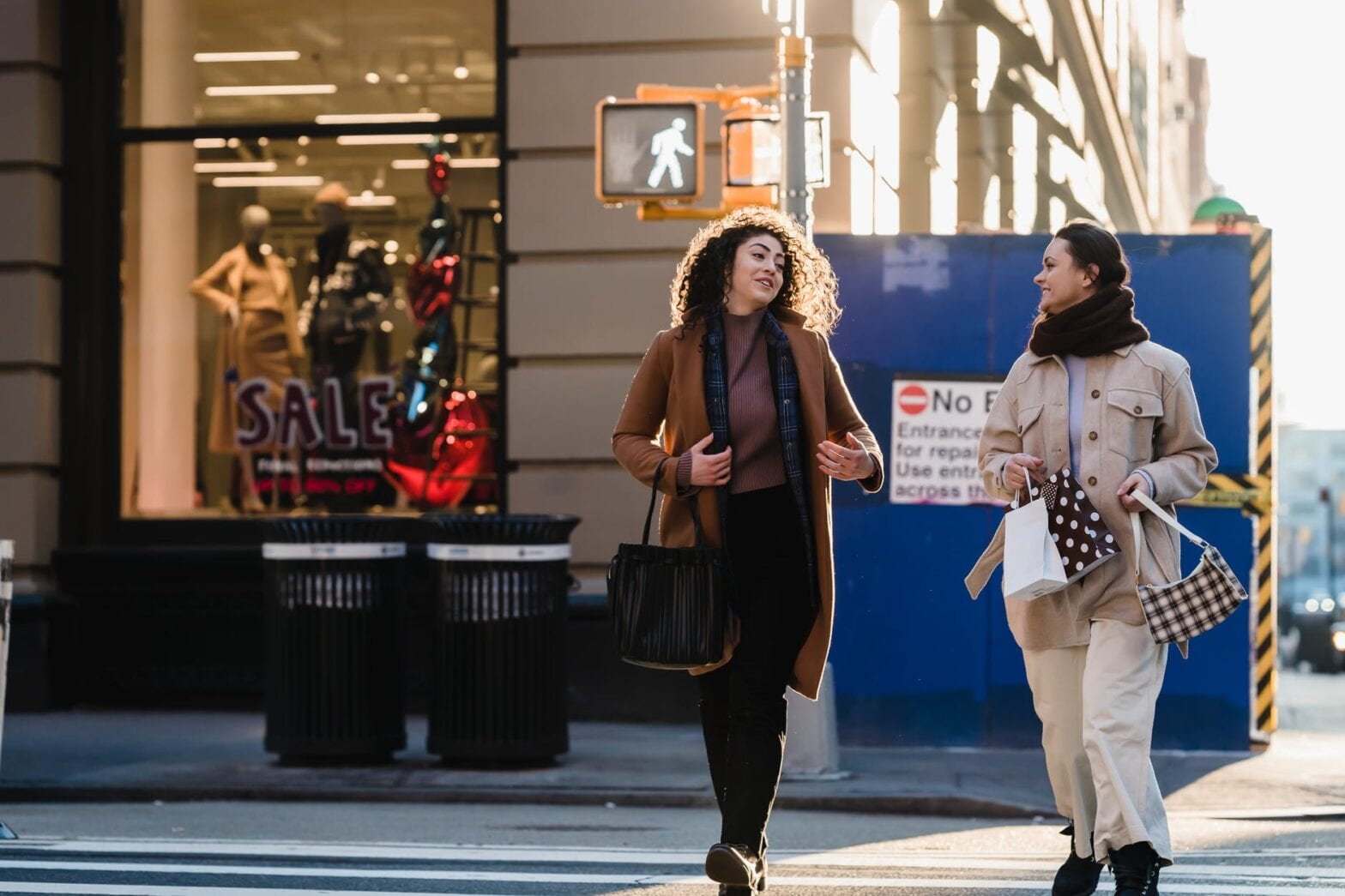 cheerful young female shopaholics crossing road near fashion store in city
